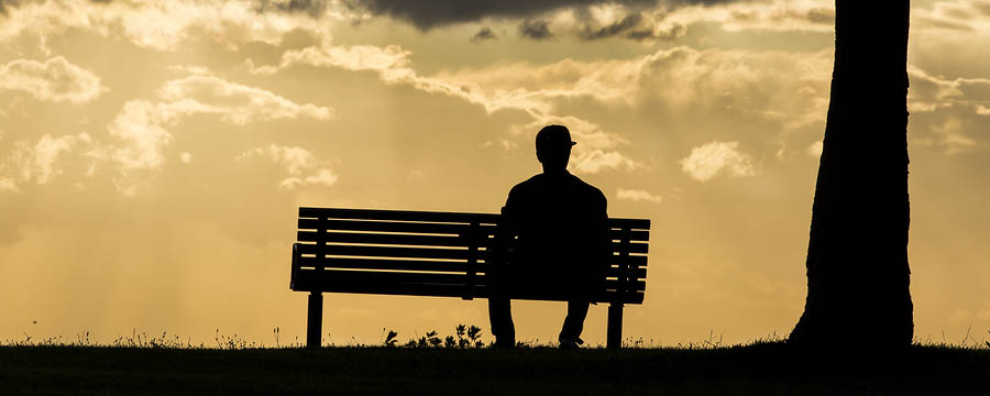 Silhouette of an anonymous man sitting on a bench alone
